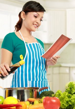 young female looking a recipe book while cooking in the kitchen photo