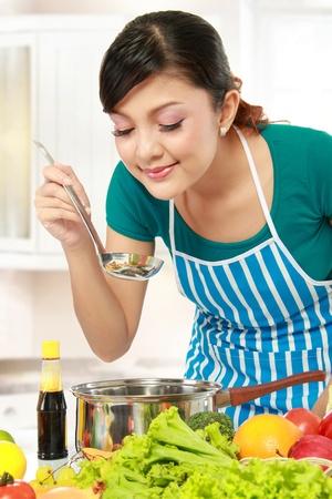mujeres cocinando: cocina hermosa mujer joven y oler la comida en la cocina Foto de archivo