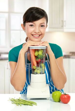 blender: Portrait of a woman posing with a blender full of fruits and vegetables in her kitchen