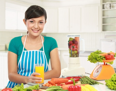 young asian woman smiling while having a glass of fresh juice in the kitchen photo
