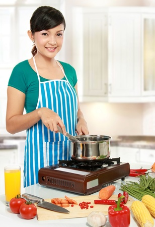 Beautiful woman cooking something in the kitchen Stock Photo - 12371527