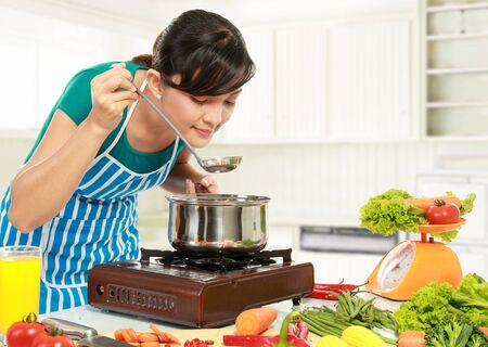 woman cooking: young woman is tasting her cooking in the kitchen Stock Photo