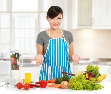 young beautiful woman in the kitchen presenting ingredient before cooking photo