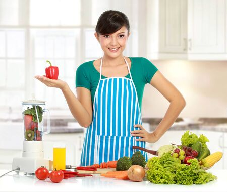 young beautiful woman in the kitchen with many ingredient ready to cook some food photo