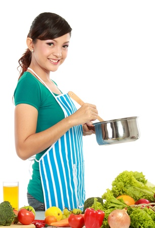 woman cooking: beautiful young women cooking something with vegetables on the table