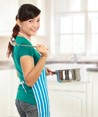 Happy young woman ready to cook some food Stock Photo - 12371514