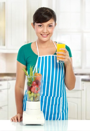 Portrait of a woman posing with a blender and orange juice in her kitchen photo
