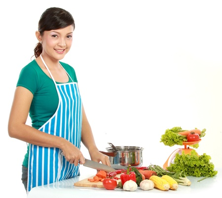 Young beautiful woman cutting vegetables on white background Stock Photo - 12371455