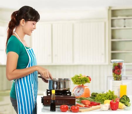 licuadora: Joven mujer sonriente cocina en la cocina