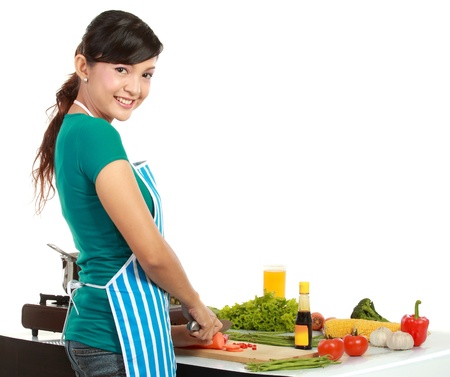 Young beautiful woman smiling cutting vegetables on white background photo