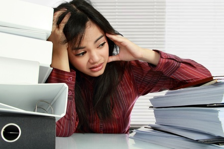 emotional stress: young business woman with many paperwork stressed in the office Stock Photo