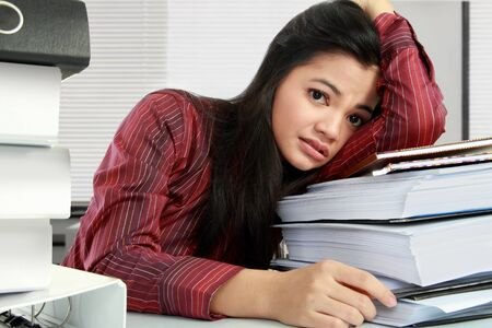 pulling: young business woman with many paperwork stressed in the office Stock Photo