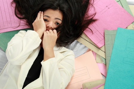 going crazy: woman lying on her paperwork. feeling stress concept Stock Photo
