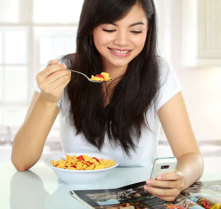 young woman having breakfast while text a message with cellphone photo