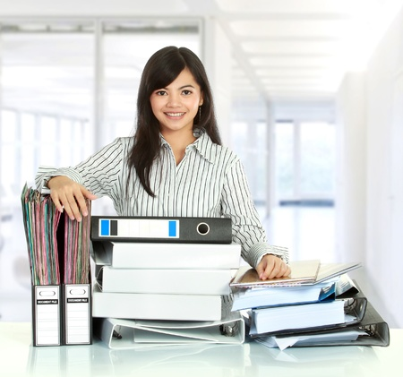 working women: Portrait of young business woman with many document on the table