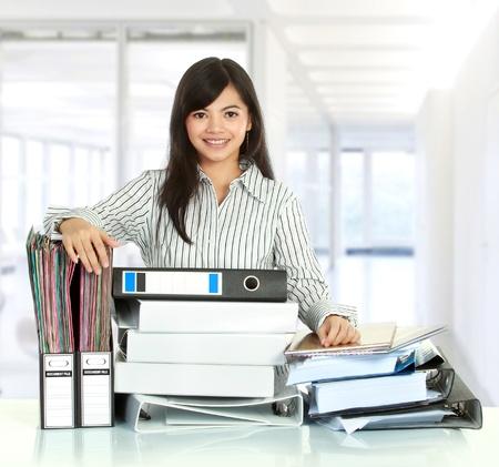 empleados trabajando: Retrato de joven mujer de negocios con el documento que muchos en la mesa