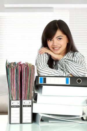 undersign: Portrait of young business woman with many document on the table