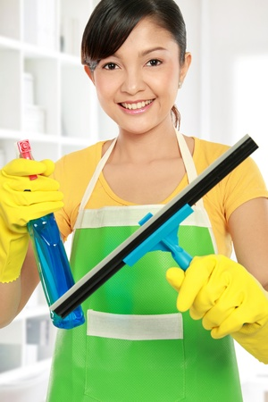 housecleaning: portrait of Attractive young woman cleaning windows Stock Photo