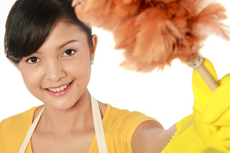 portrait of beautiful asian woman cleaning using duster isolated over white background photo