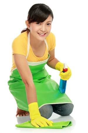 attractive asian woman cleaning the floor while kneeling at home photo