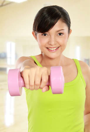 Portrait of pretty young woman using dumbbells during exercising Stock Photo - 12371588
