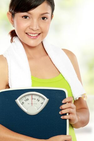 Young fitness woman carrying a weight scale Stock Photo - 12371656
