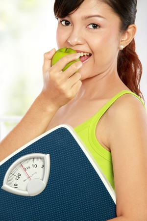 healthy fitness woman carrying a weight scale while eating fresh green apple photo