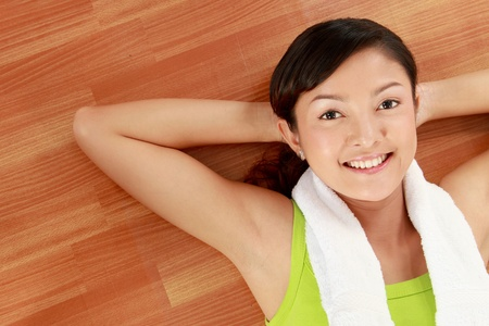 Portrait of gorgeous young female smiling while lying on gym floor photo