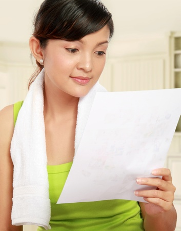 Portrait of healthy young woman reading healthy menu photo