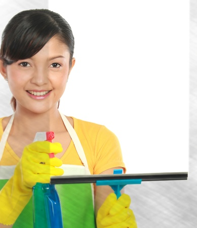 portrait of Attractive young woman cleaning windows. copy space for your text photo