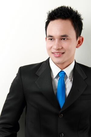 Closeup portrait of a happy young asian businessman smiling on white background Stock Photo - 12799076