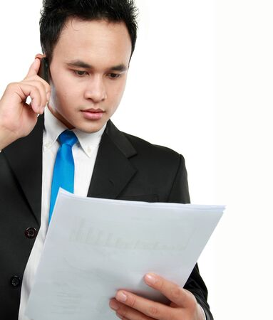 Young businessman holding a report and talking to mobile phone photo