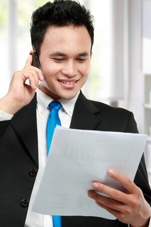 Happy executive reading a report while calling by phone photo