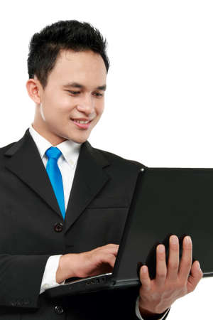 young business man using laptop while standing over white background photo