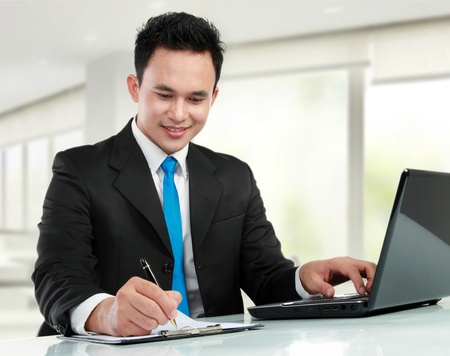 Portrait of a handsome young business man with laptop and pen working Stock Photo - 12798813