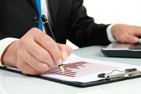 Businessmans hand looking at diagram on financial report Stock Photo