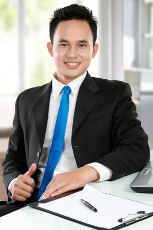1 man only: Happy handsome young asian business man at the office