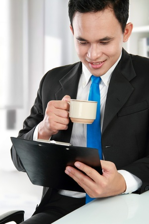 Portrait of a businessman reading document while having a cup of tea photo