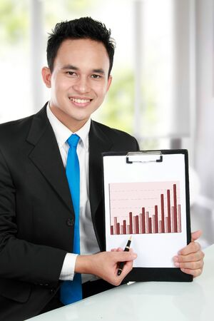 smiling young business man showing growth chart diagram photo