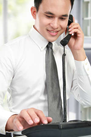 smiling asian business man reading a report while calling by phone photo