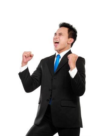 achieved: Cheerful asian business man with arms raised in success isolated on white background
