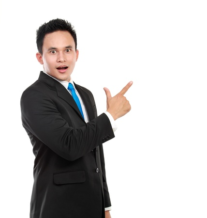 Portrait of a successful young business man surprisingly pointing at something isolated against white background photo