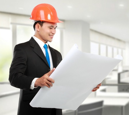 confident Handsome young asian man architect looking at paper print in the office Stock Photo - 12799656
