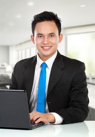 podnikatel: Portrét pohledný mladý muž s přenosným počítačem pracují v kanceláři
