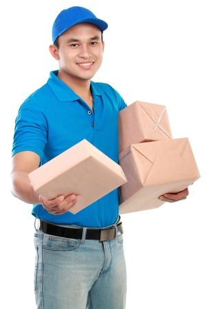 delivery package: Young man courier in blue uniform with packages isolated on white Stock Photo