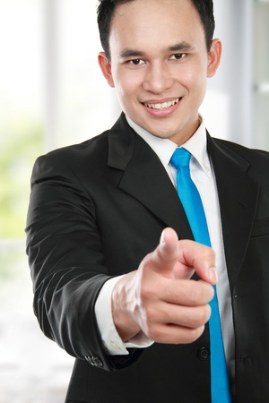 Portrait of a smiling young business man pointing at you photo