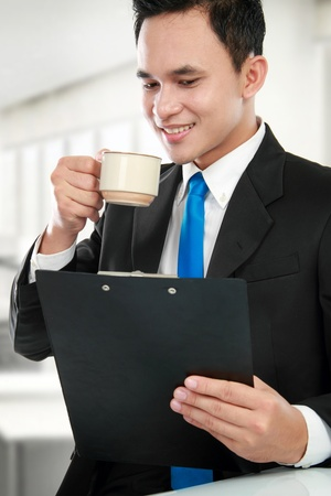 financial report: Happy executive reading a report while drinking Stock Photo
