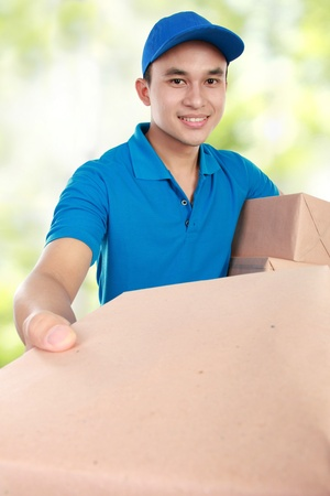 Young man courier in blue uniform giving a package photo