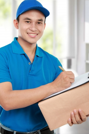smiling delivery man in blue uniform with packages and clipboard photo