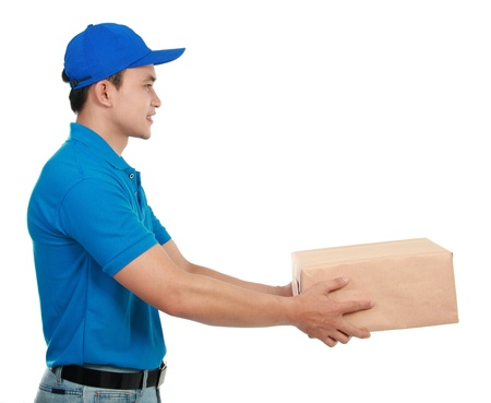 delivery man: Young man courier in blue uniform streching out his hand to give the packages Stock Photo